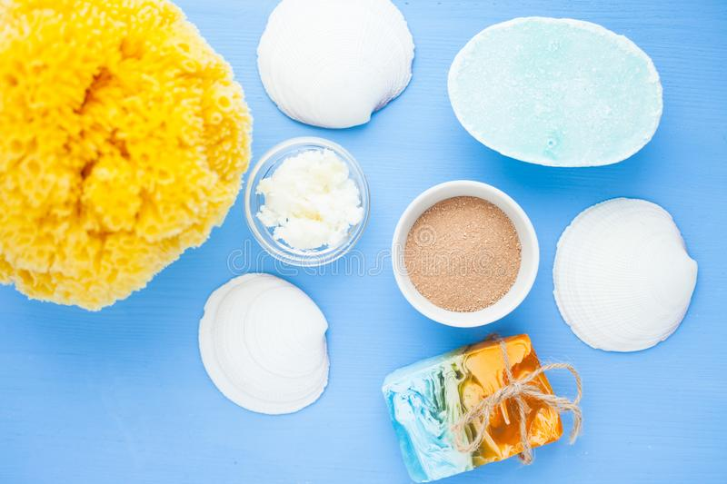Spa and natural cosmetics concept. Set of skin and body care tools: shea oil, seashells, sponges, soap, clay and seaweed on the bright background. Top view royalty free stock photo