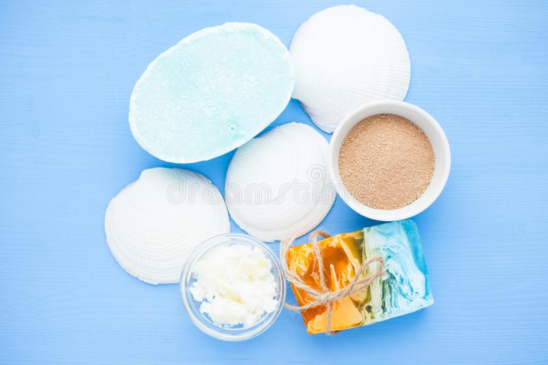 Spa and natural cosmetics concept. Set of skin and body care tools: shea oil, seashells, sponges, soap, clay and seaweed on the bright background. Top view royalty free stock photography