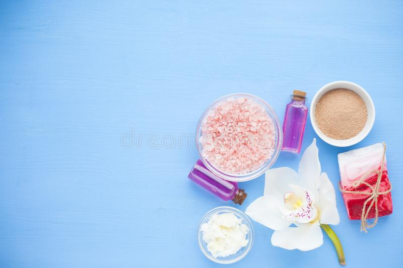 Spa and natural cosmetics concept. Set of skin and body care tools: shea oil, seashells, sponges, soap, clay and seaweed on the bright background. Top view royalty free stock image
