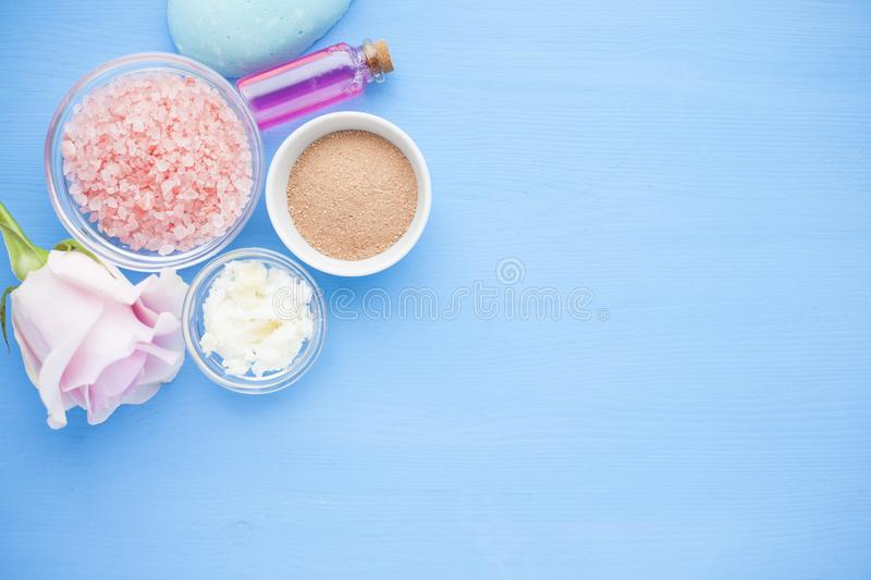 Spa and natural cosmetics concept. Set of skin and body care tools: shea oil, seashells, sponges, soap, clay and seaweed on the bright background. Top view stock image