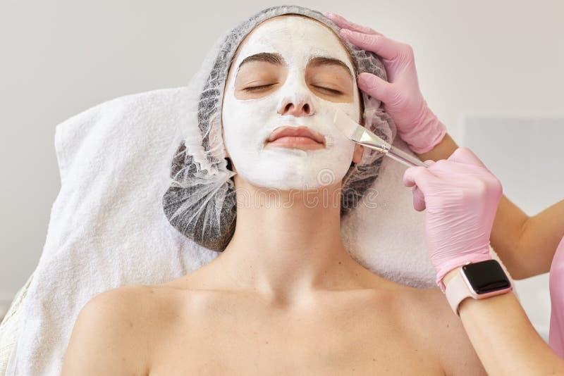 Spa och hudomsorgbegrepp Ung kvinna med den ansikts- maskeringen i skönhetsalong, cosmetologist som använder på den speciala bors royaltyfria bilder