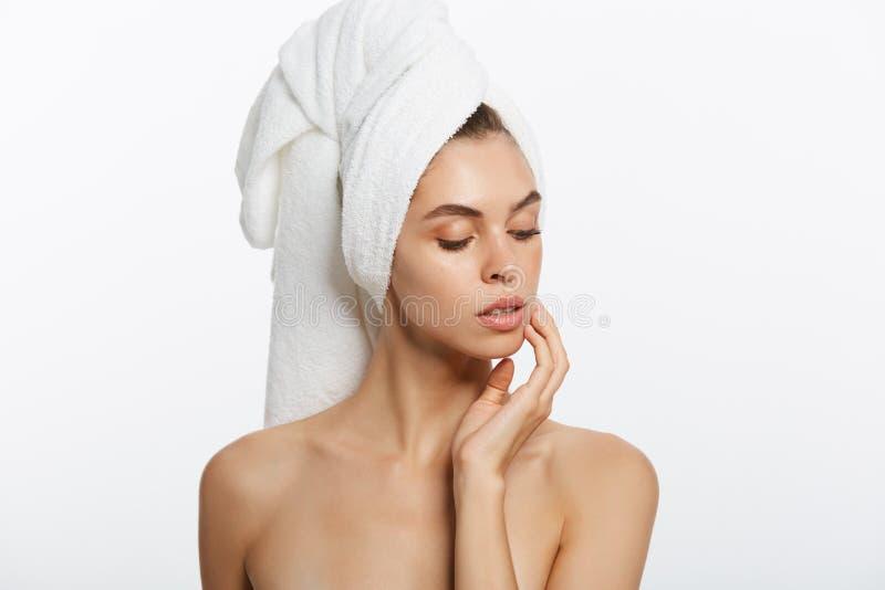 Spa och skönhetbegrepp - den lyckliga unga flickan med ren hud och med en vit handduk på hennes head washes vänder mot royaltyfri bild