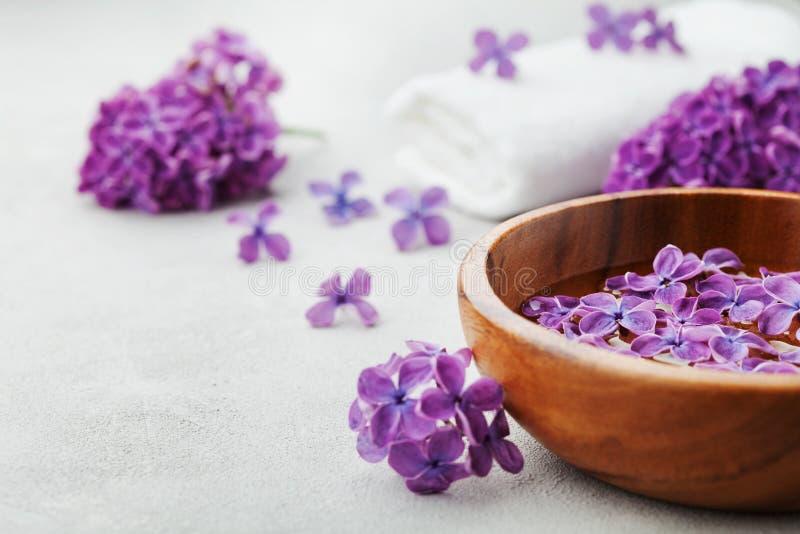 Spa och wellnesssammansättning med parfymerat lilablommavatten i träbunke och frottéhandduk på stenbakgrund, aromatherapy arkivbild