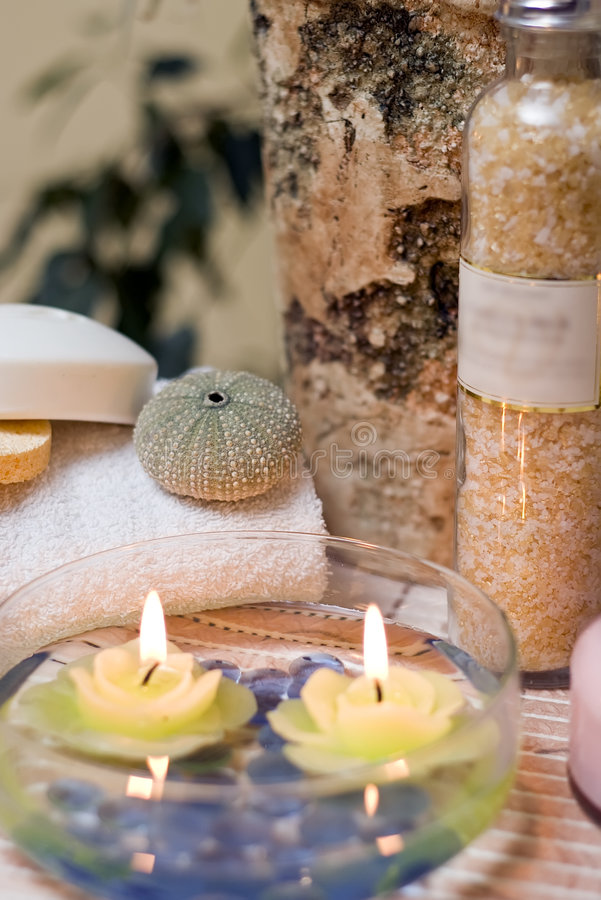Spa orchid composition. A spa composition consisting of bottle, towel, sea shell and candles submerged in a glass bowl with water stock image