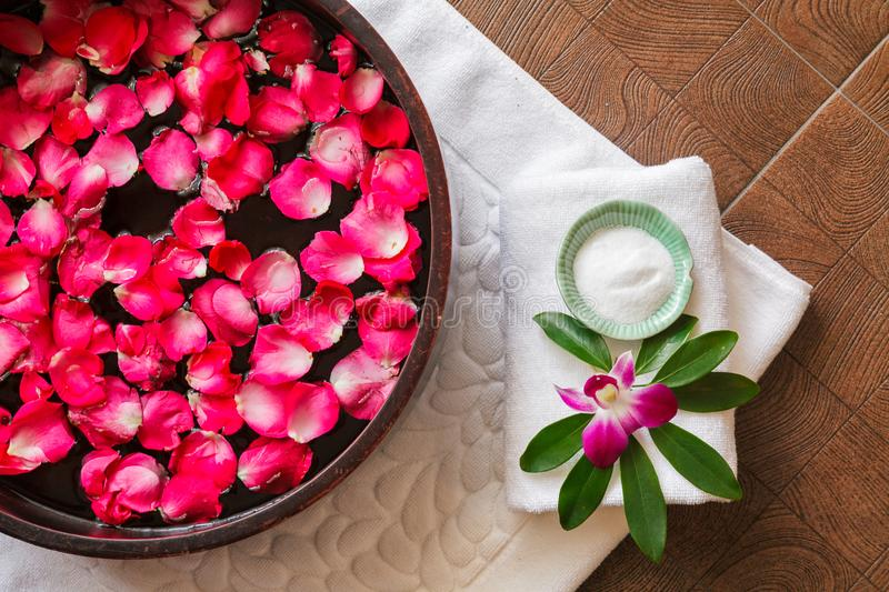 Spa pedicure treatment with foot bath in bowl, red rose petals ,orchid,foot scrub ,. Top view royalty free stock photography