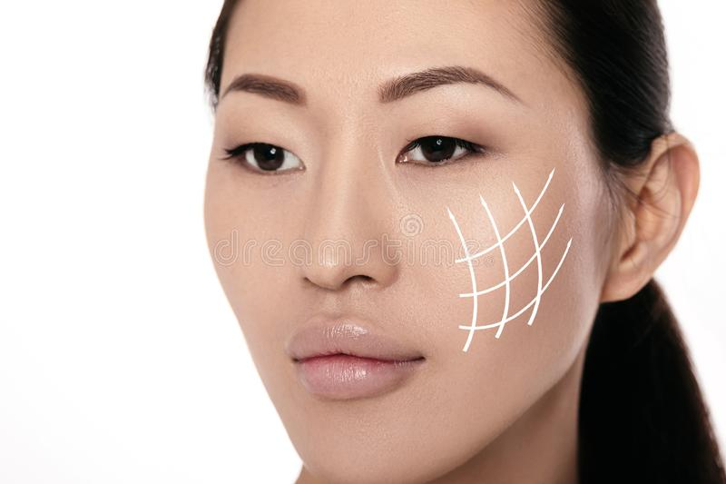 Spa portrait of attractive asian woman with arrows on her face. On white background. Face lifting concept. Plastic surgery treatment, medicine royalty free stock photos