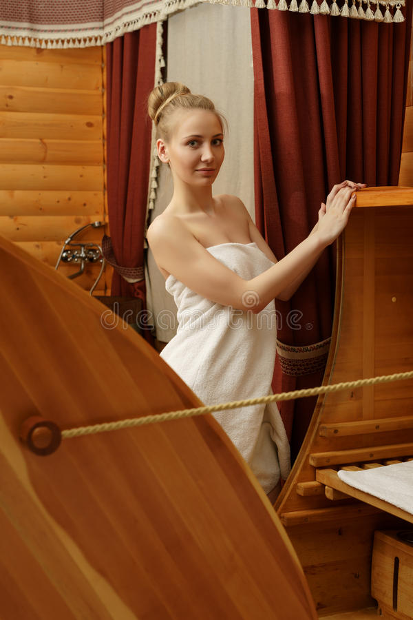 In spa. Pretty woman posing with cedar hot tub royalty free stock photography