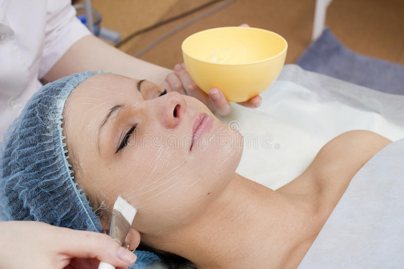 Spa procedure. The young woman lies on a white background and it smear with a cream royalty free stock photos