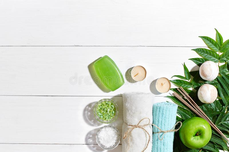 Spa products. Bath salts, soap, candles and towel. Flat lay on white wooden background, top view. royalty free stock images