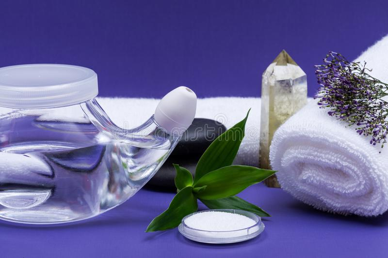 Spa purple background with Neti Pot, pile of Saline, rolled up White Towels, stacked Basalt Stones and Bamboo Leaves. Sinus wash. Nasal irrigation royalty free stock image