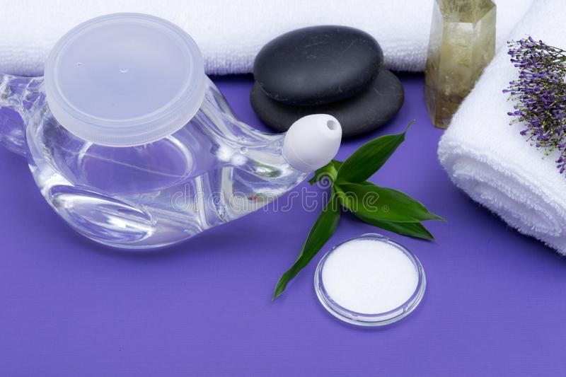 Spa purple background with Neti Pot, pile of Saline, rolled up White Towels, stacked Basalt Stones and Bamboo Leaves. Sinus wash. Nasal irrigation stock images