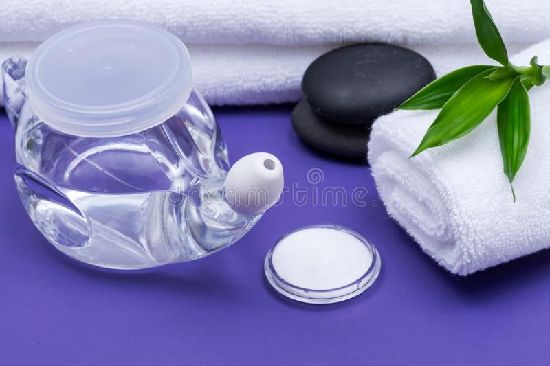 Spa purple background with Neti Pot, pile of Saline, rolled up White Towels, stacked Basalt Stones and Bamboo Leaves. Sinus wash. Nasal irrigation royalty free stock photos