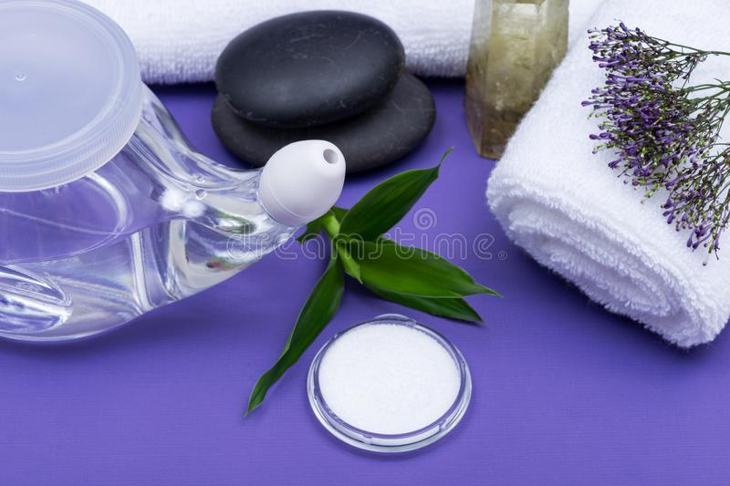 Spa purple background with Neti Pot, pile of Saline, rolled up White Towels, stacked Basalt Stones and Bamboo Leaves. Sinus wash. Nasal irrigation royalty free stock images