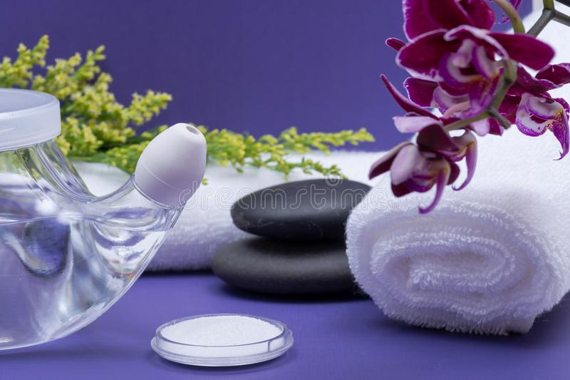 Spa purple background with Neti Pot, pile of Saline, rolled up White Towels, stacked Basalt Stones and Orchid Flower. Sinus wash. Nasal irrigation stock photos