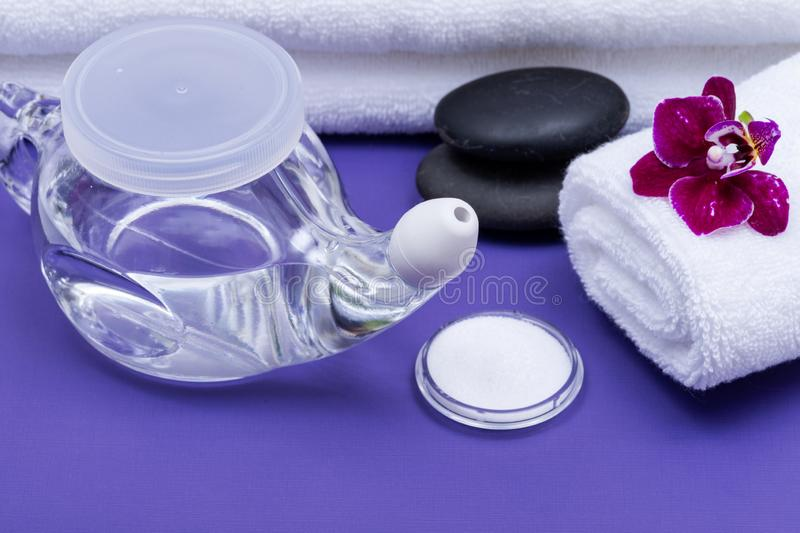 Spa purple background with Neti Pot, pile of Saline, rolled up White Towels, stacked Basalt Stones and Orchid Flower. Sinus wash. Nasal irrigation stock images