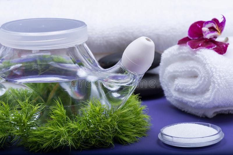 Spa purple background with Neti Pot, pile of Saline, rolled up White Towels, stacked Basalt Stones and Orchid Flower. Sinus wash. Nasal irrigation stock photo