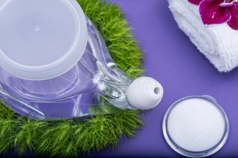 Spa purple background with Neti Pot, pile of Saline, rolled up White Towels, stacked Basalt Stones and Orchid Flower. Sinus wash. Nasal irrigation stock image