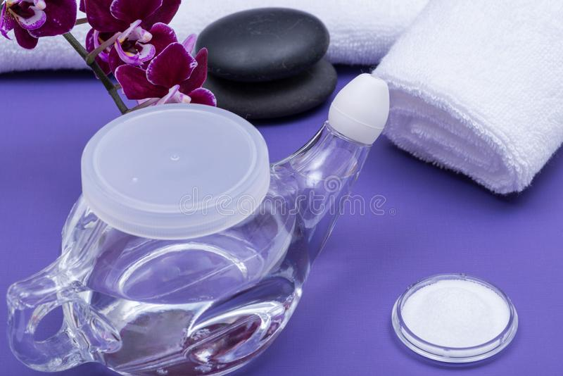Spa purple background with Neti Pot, pile of Saline, rolled up White Towels, stacked Basalt Stones and Orchid Flower. Sinus wash. Nasal irrigation royalty free stock image