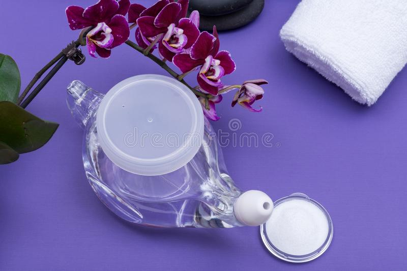 Spa purple background with Neti Pot, pile of Saline, rolled up White Towels, stacked Basalt Stones and Orchid Flower. Sinus wash. Nasal irrigation royalty free stock photos