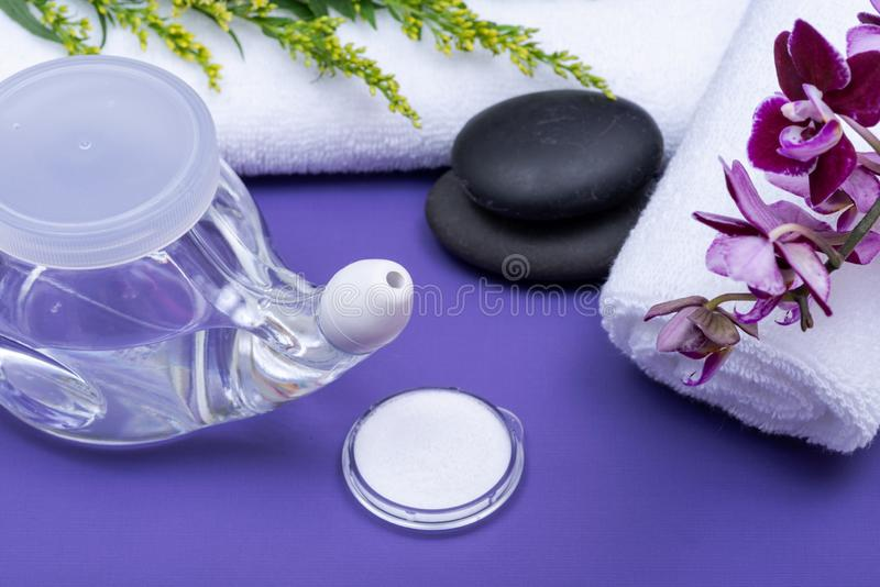 Spa purple background with Neti Pot, pile of Saline, rolled up White Towels, stacked Basalt Stones and Orchid Flower. Sinus wash. Nasal irrigation royalty free stock images