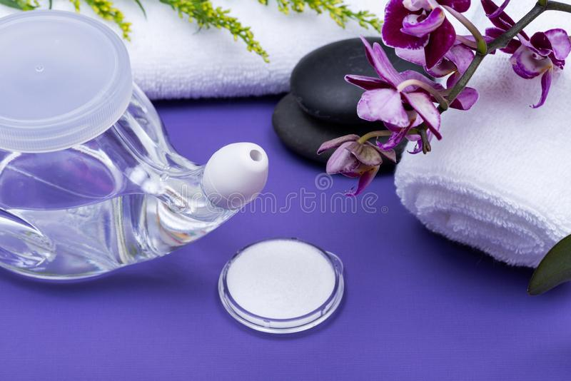 Spa purple background with Neti Pot, pile of Saline, rolled up White Towels, stacked Basalt Stones and Orchid Flower. Sinus wash. Nasal irrigation stock photography