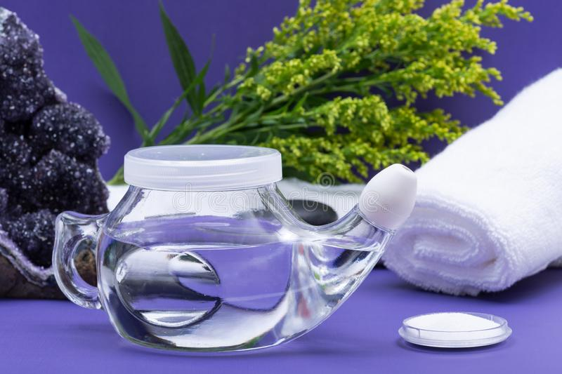 Spa purple background with Neti Pot, pile of Saline, rolled up White Towels and stacked Basalt Stones. Sinus wash. Nasal irrigation royalty free stock images