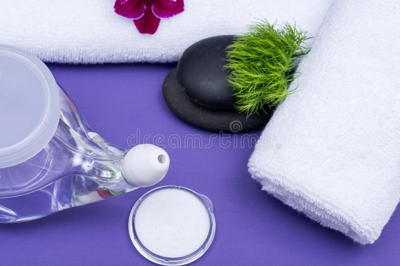 Spa purple background with Neti Pot, pile of Saline, rolled up White Towels and stacked Basalt Stones. Sinus wash. Nasal irrigation royalty free stock photos
