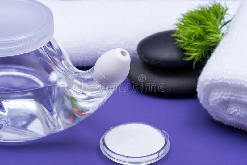 Spa purple background with Neti Pot, pile of Saline, rolled up White Towels and stacked Basalt Stones. Sinus wash. Nasal irrigation royalty free stock image