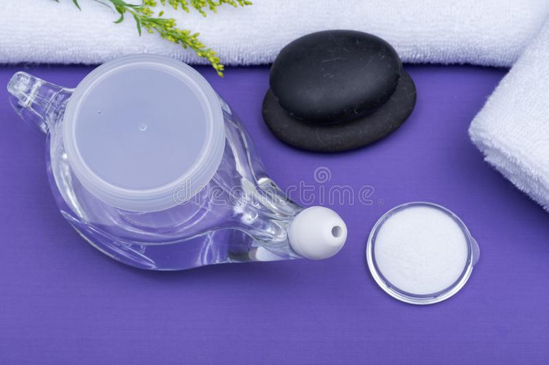 Spa purple background with Neti Pot, pile of Saline, rolled up White Towels and stacked Basalt Stones. Sinus wash. Nasal irrigation royalty free stock photo
