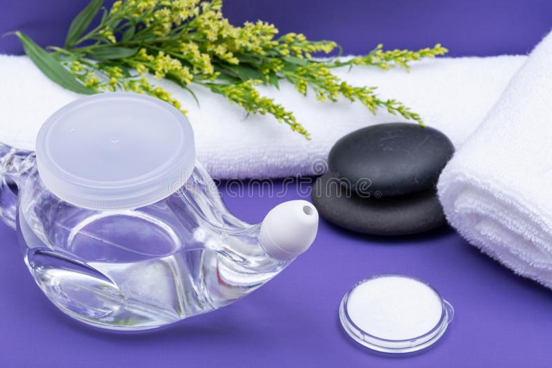 Spa purple background with Neti Pot, pile of Saline, rolled up White Towels and stacked Basalt Stones. Sinus wash. Nasal irrigation stock images