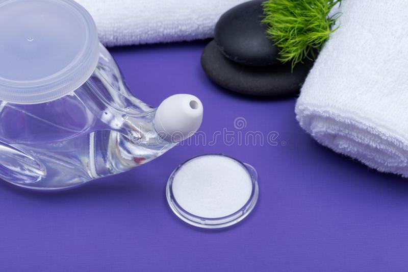 Spa purple background with Neti Pot, pile of Saline, rolled up White Towels and stacked Basalt Stones. Sinus wash. Nasal irrigation stock photos