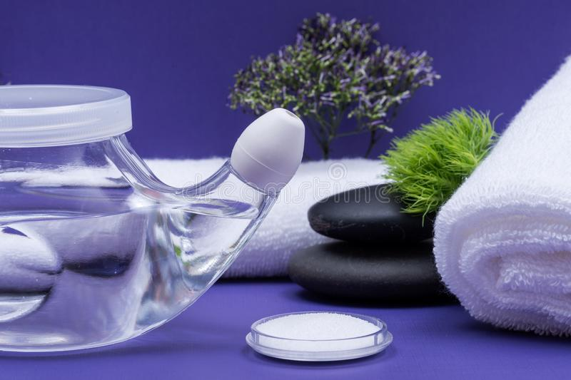 Spa purple background with Neti Pot, pile of Saline, rolled up White Towels and stacked Basalt Stones. Sinus wash. Nasal irrigation stock image