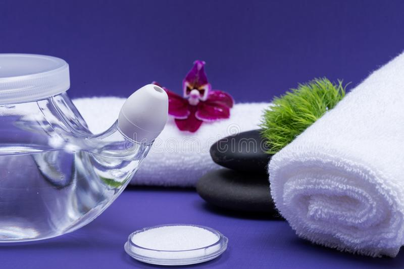 Spa purple background with Neti Pot, pile of Saline, rolled up White Towels and stacked Basalt Stones. Sinus wash. Nasal irrigation stock photo
