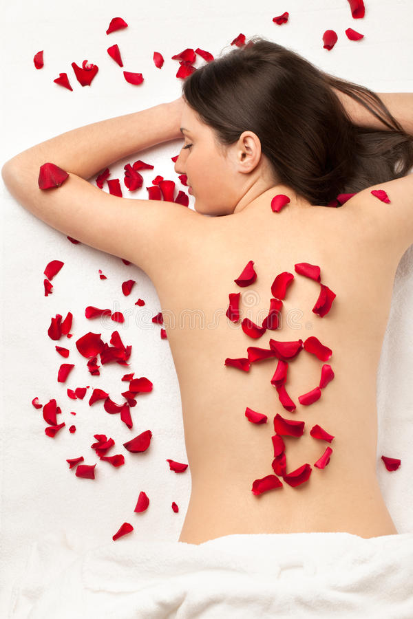 Spa relax. Girl with word SPA made of roses' petals royalty free stock photos