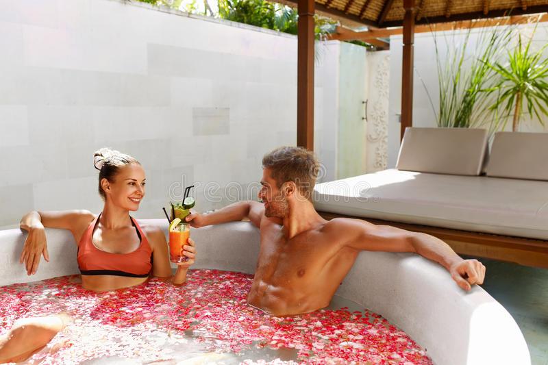 Spa Relax. Couple In Love In Flower Bath Drinking Drinks royalty free stock image