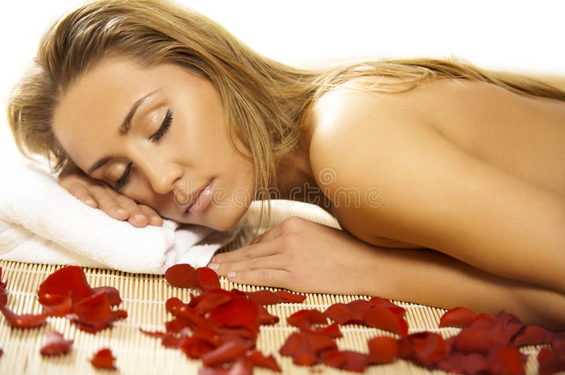 Spa Relaxing V. Portrait of Fresh and Beautiful blond woman laying on bamboo mat around flowers and taking spa treatment stock image