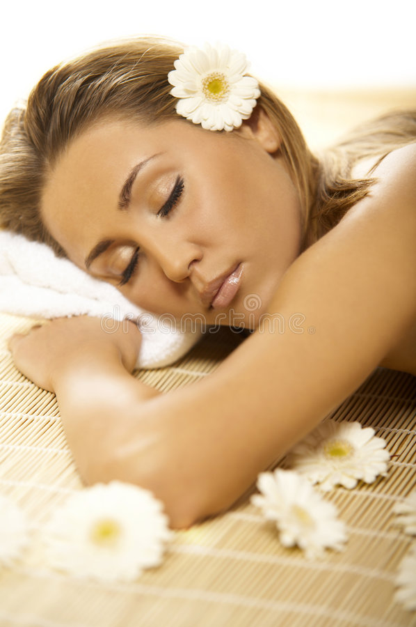 Spa Relaxing V. Portrait of Fresh and Beautiful blond woman laying on bamboo mat around flowers and taking spa treatment royalty free stock image