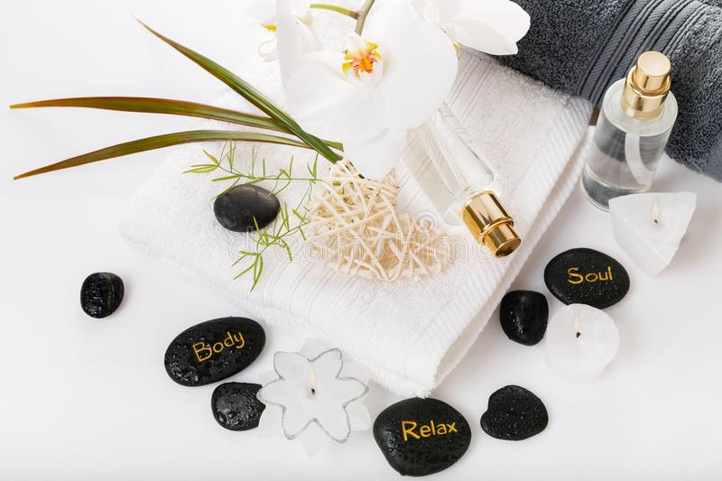 Spa resort therapy composition. Burning candles, stones, towel, abstract lights. Spa resort therapy composition. Burning candles, black stones, towel, orchid royalty free stock photography