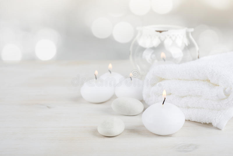 Spa resort therapy composition. Burning candles, stones, towel, abstract lights royalty free stock photos