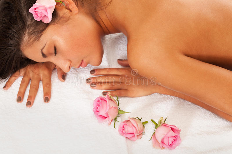 Spa and roses. Girl with eyes closed laying on a towel with roses stock photos