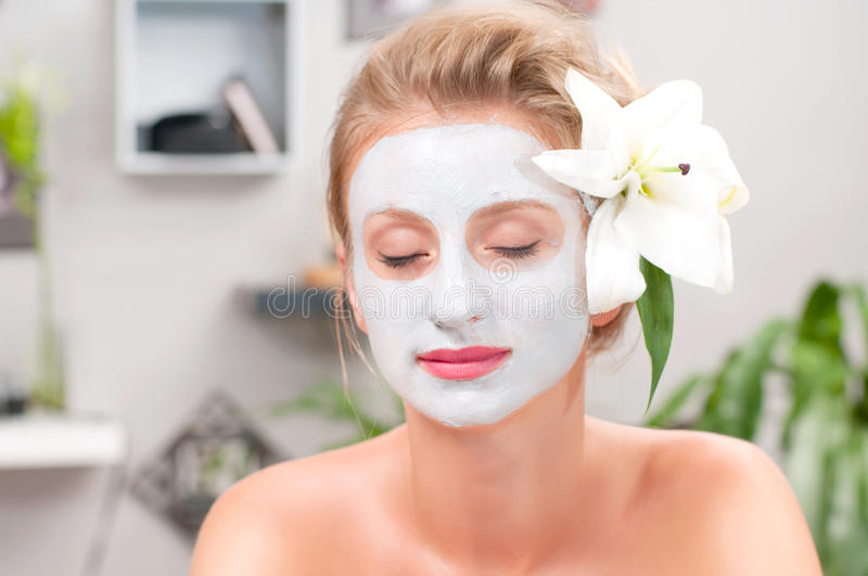 Spa salon. Beautiful woman with clay facial mask at beauty salon. Beauty treatment and spa salon. Beautiful woman with clay facial mask at beauty salon royalty free stock photos