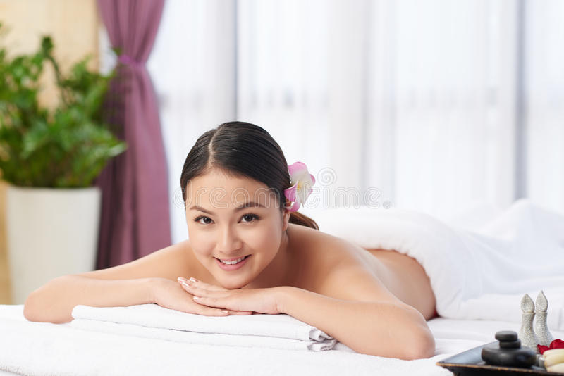 In spa salon. Cheerful pretty Asian woman lying on massage table royalty free stock photo