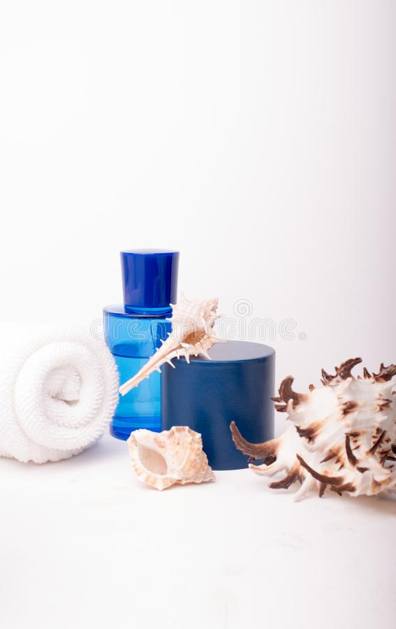 Spa salon concept with rolled white towel, blue bottle and seashells on white wooden background. Spa treatments. Spa background. S. Pace for a text stock photography