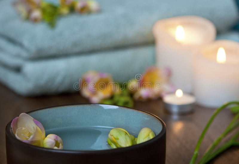 Spa scene. With candles, green towels and green bowl with water and flowers stock photo
