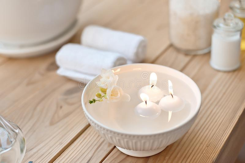 Spa set with candles in aroma bath and rolled towels on wooden table.  royalty free stock photography