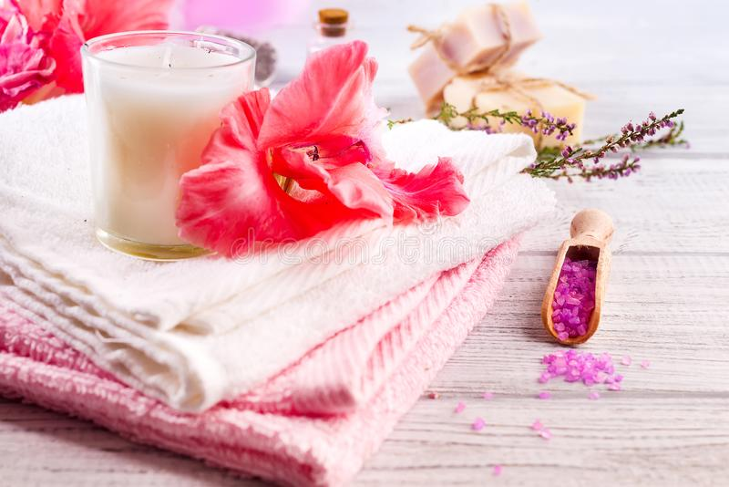 Spa set with flower, candle, bath soap and massage salt on wooden background stock images