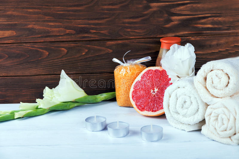 Spa set with flowers, sea salt, gel shower, towels, scrubs and wisp on white wooden table. With copy space. Spa set with flowers, sea salt in packets, gel royalty free stock photo