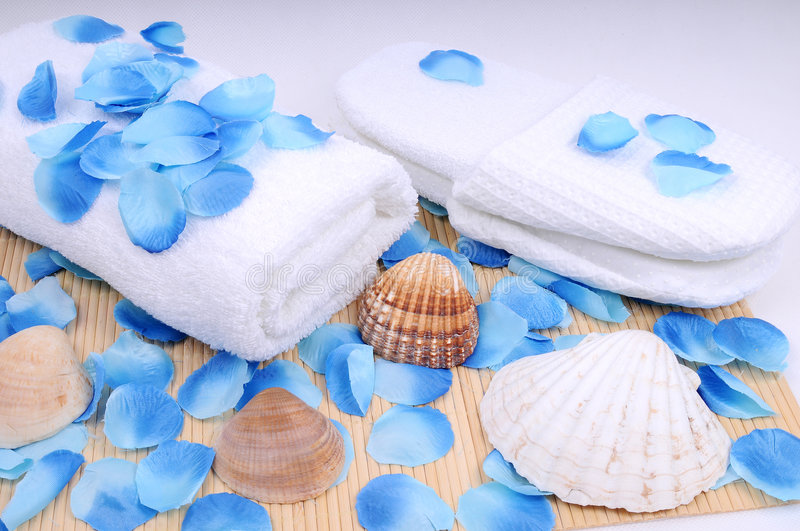 Spa set, towel and conch. Spa preaparation - white towel covered with blue petal royalty free stock photography