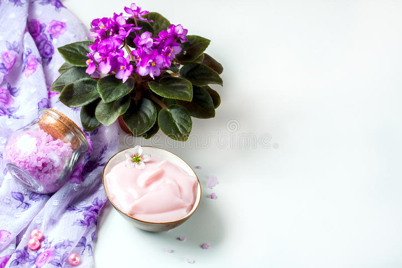 Spa setting with cosmetic cream, bath salt and African violet in flower pot on white wooden table background. Selective focus stock photo