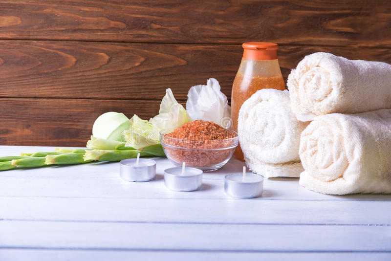 Spa setting with natural olive bath boamb, sea salt, scrub, flowers, towels and candles. On a white wooden table. with copy royalty free stock photography